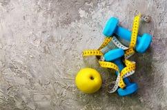 Turkooise domoren met het meten van band en gele appel op concrete achtergrond Vrije ruimte voor uw tekst Het concept van de spor Stock Afbeelding