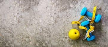 Turkooise domoren met het meten van band en gele appel op concrete achtergrond Vrije ruimte voor uw tekst Het concept van de spor Stock Foto