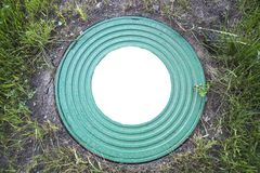 Turkos för väl gjutjärn för lucka tung med en modell av många cirklar på en bakgrund av grönt gräs I mitten av den vita rundan arkivbild