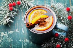 Turkos rånar av jul funderad vin eller gluhwein med kryddor och apelsinskivor på träkrickatabellen Traditionell drink på vinter royaltyfri fotografi
