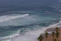 Turkosblåtthavvågor på sand sätter på land med palmträd Arkivfoton