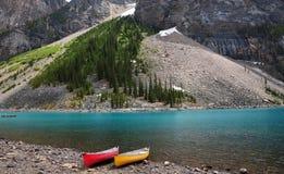 Turkosfärgmorän sjö med den röda och gula kanoten i den Banff nationalparken som lokaliseras i kanadensiska steniga berg i Albert fotografering för bildbyråer