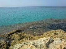 Turkoshav av kristallklart vatten från stenig kust royaltyfria foton