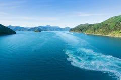 Turkosvatten med tvättar sig skapat av passagerareskeppet som går mot Picton till och med drottningen Charlotte Sound med den fro royaltyfri bild