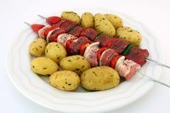 Turks rundvlees, lam, en varkensvlees kebabs met aardappel op vleespennen royalty-vrije stock foto