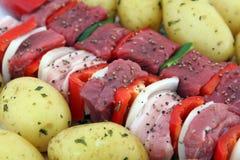 Turks rundvlees, lam, en varkensvlees kebabs met aardappel op vleespennen Stock Foto
