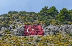 Turkse die vlag in de bergstad wordt geschilderd van Finike Turkije Stock Fotografie