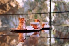 Turkse koffie twee in koper cezve met stuk van lokum op de glaslijst Stock Foto's