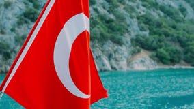 Turkse vlag die op wind op achtergrond van overzeese kust en bergen golven stock video