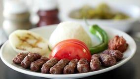 Turkse vleesballetjeinegol kofte met rijst, ui, tomaten en groene paprika Roterend schot Langzame Motie stock videobeelden