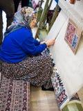 Turkse Vrouw die een Tapijt maken Stock Afbeeldingen