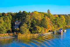 Turku Archipelago with fall season colors. Small wooden jetty pier building on Turku Archipelago, in front of a log house in the autumn-coloured forest, Finland Stock Images