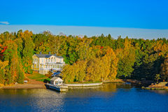 Turku Archipelago with fall season colors. Small wooden jetty pier building on Turku Archipelago, in front of a log house in the autumn-coloured forest, Finland Royalty Free Stock Photography