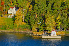 Turku Archipelago with fall season colors. Small wooden jetty pier building on Turku Archipelago, in front of a log house in the autumn-coloured forest, Finland Stock Photography