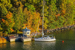 Turku Archipelago with fall season colors. Yacht moored on small wooden jetty pier building on Turku Archipelago in the autumn-coloured forest, Finland Royalty Free Stock Photography