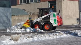 Small front loader clean up the street from the snow. Turku, Finland. TURKU, FINLAND - FEBRUARY 23, 2018: Small front loader clean up the street from the snow stock video