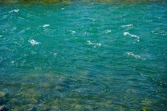 Turkusowa woda rzeczna z małymi fala i kamieniami fotografia royalty free