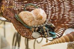 Turkusowego błękita etniczna kolia i skorupy nad słomianym koszem Obrazy Royalty Free