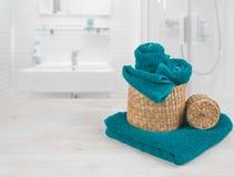 Turkusowi zdrojów ręczniki i łozinowi kosze na defocused łazienki wnętrzu Fotografia Stock