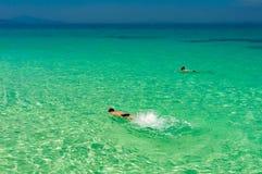 Turkusowy kryształ - jasny morze z mężczyzna robi snorkeling w wodny pobliskim Zdjęcia Stock