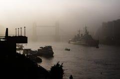 Turm-Brücke, London, in einem dichten Nebel mit einem Militärschlachtschiff in der Front Lizenzfreie Stockfotografie