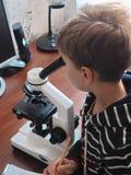 Turma de Biologia Menino novo em um laboratório de ciência que estuda amostras sob o microscópio Vista através do microscópio óti Foto de Stock