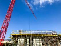 Turmbaukran gegen den blauen Himmel und die Sonne Bau von Neubauten mit einem Kran Roter Turmkran Lizenzfreie Stockfotos