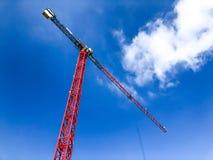 Turmbaukran gegen den blauen Himmel und die Sonne Bau von Neubauten mit einem Kran Roter Turmkran Stockfoto