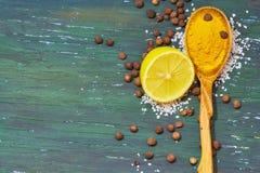Turmeric σε ένα ξύλινο κουτάλι λεμόνι, άλας, στοκ εικόνες