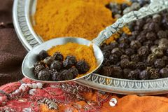 Turmeric and black pepper combination has great heath benefits. Turmeric and black pepper on spoon and metal plate Stock Photo