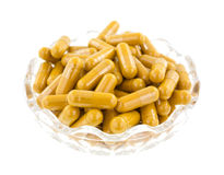 Turmeric capsules in a bowl Royalty Free Stock Photos