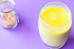 Turmeric with Coconut Milk Drinks and Ghee on Purple Background Good for Beauty and Health, Gives a lot of Energy, Close-up Stock Image