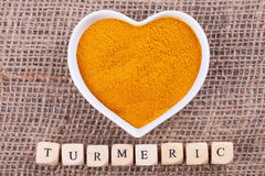 Turmeric in  cup. In the shape of heart on sack  cloth Royalty Free Stock Photography