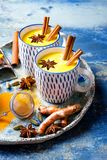 Turmeric golden milk latte with cinnamon sticks and honey. Detox, immune boosting, anti inflammatory healthy cozy drink. Turmeric golden milk latte with royalty free stock photo