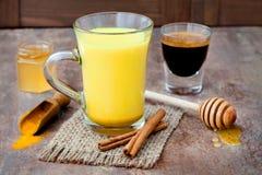 Turmeric golden milk latte with cinnamon sticks and honey. Detox liver fat burner, immune boosting, anti inflammatory drink Stock Images