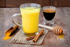 Turmeric golden milk latte with cinnamon sticks and honey. Detox liver fat burner, immune boosting, anti inflammatory drink. Turmeric golden milk latte with Stock Image