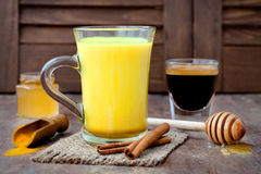 Turmeric golden milk latte with cinnamon sticks and honey. Detox liver fat burner, immune boosting, anti inflammatory drink. Turmeric golden milk latte with Stock Images