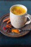 Turmeric golden milk latte with cinnamon sticks Royalty Free Stock Photo