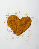 Turmeric heart. Turmeric powder sprinkled into the shape of a heart. Turmeric is widely considered to be a superfood. This image was shot on a natural colored Stock Photos