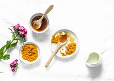 Turmeric, honey, coconut milk face mask. Homemade ingredients beauty products on a light background, top view. Beauty, skin care concept stock photo