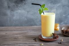 Turmeric Lassi Drink. Turmeric Lassie or lassi in glass - Healthy Probiotic Indian cold drink made up of curd yogurt, milk, spices and sugar. Turmeric Smoothie stock photo