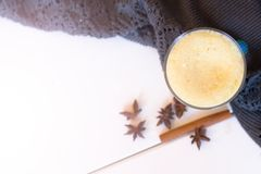 Turmeric latte and a warm blanket at sunset. the concept of comfort. read bestseller. warm home. Turmeric Latte with Nut Milk, cin Stock Photo
