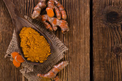 Turmeric. Portion of Turmeric (selective focus) on an old wooden table Stock Image