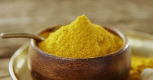 Turmeric powder in bowl on a plate 4k. Close-up of turmeric powder in bowl on a plate 4k stock footage