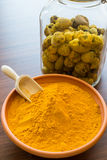Turmeric powder. In bowl and raw turmeric in jar on background stock image