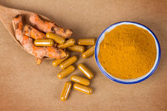 The turmeric powder and capsule and roots curcumin on brown pape. R Royalty Free Stock Images