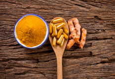 turmeric powder , capsule and roots curcumin on wooden plate Stock Image