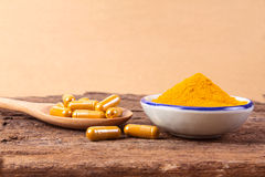 Turmeric powder , capsule and roots curcumin on wooden plate Royalty Free Stock Photo