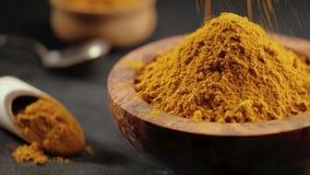 Turmeric powder or curcuma powder falling in a wooden bowl