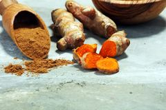 Turmeric powder and fresh turmeric on grey background Stock Image